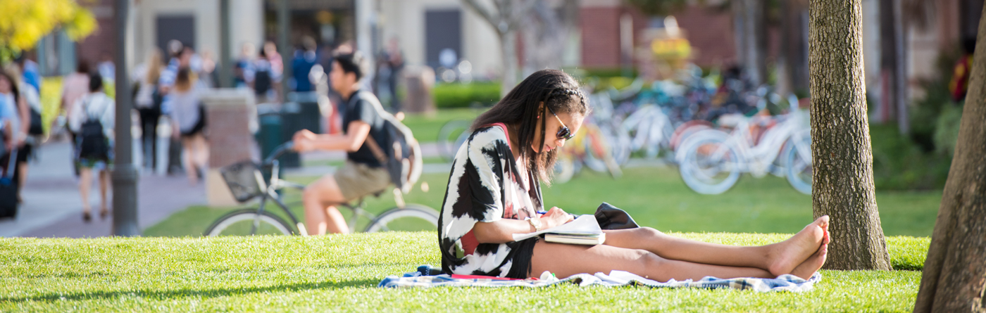 Student studying in the grass on campus